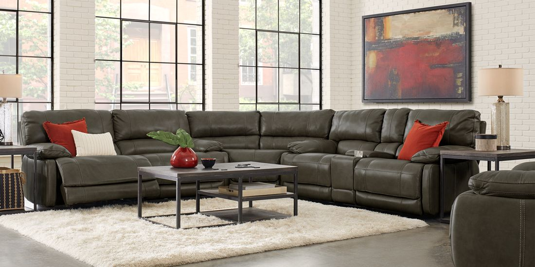 Dark Gray Cindy Crawford Sectional with Red and Orange Decor Contrasted by a White Shag Rug